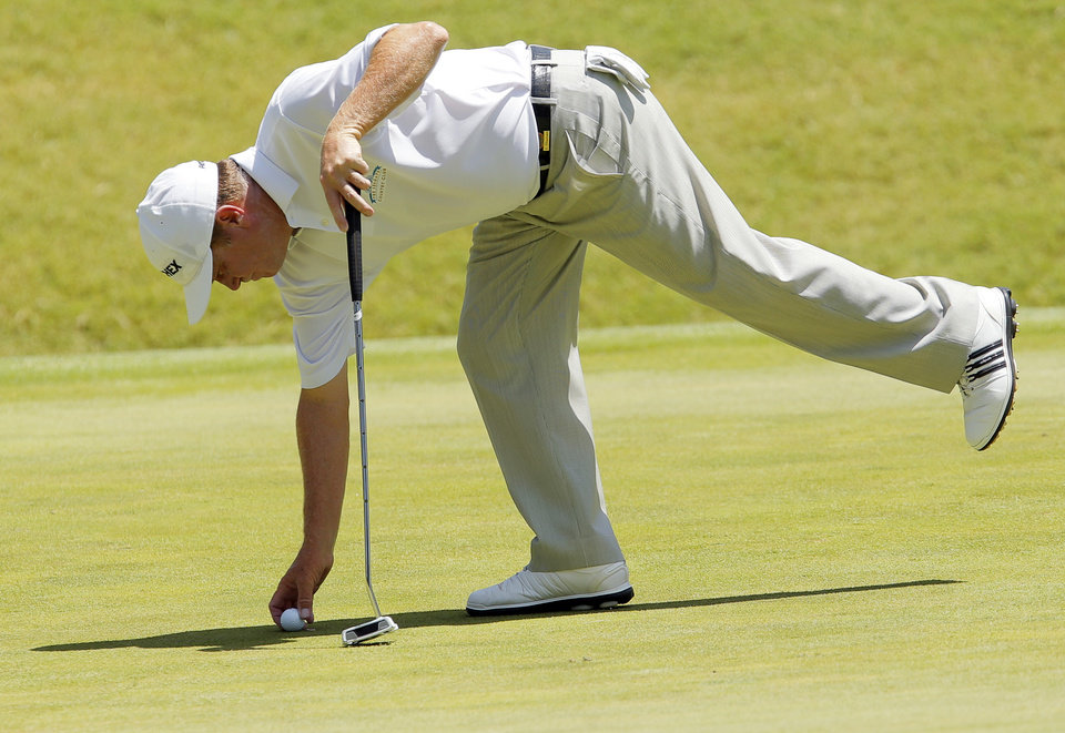 Photo - Jeff Sluman places his ball on the No. 4 green during the final round of the U.S. Senior Open golf tournament at Oak Tree National in Edmond, Okla., Sunday, July 13, 2014. Photo by Nate Billings, The Oklahoman