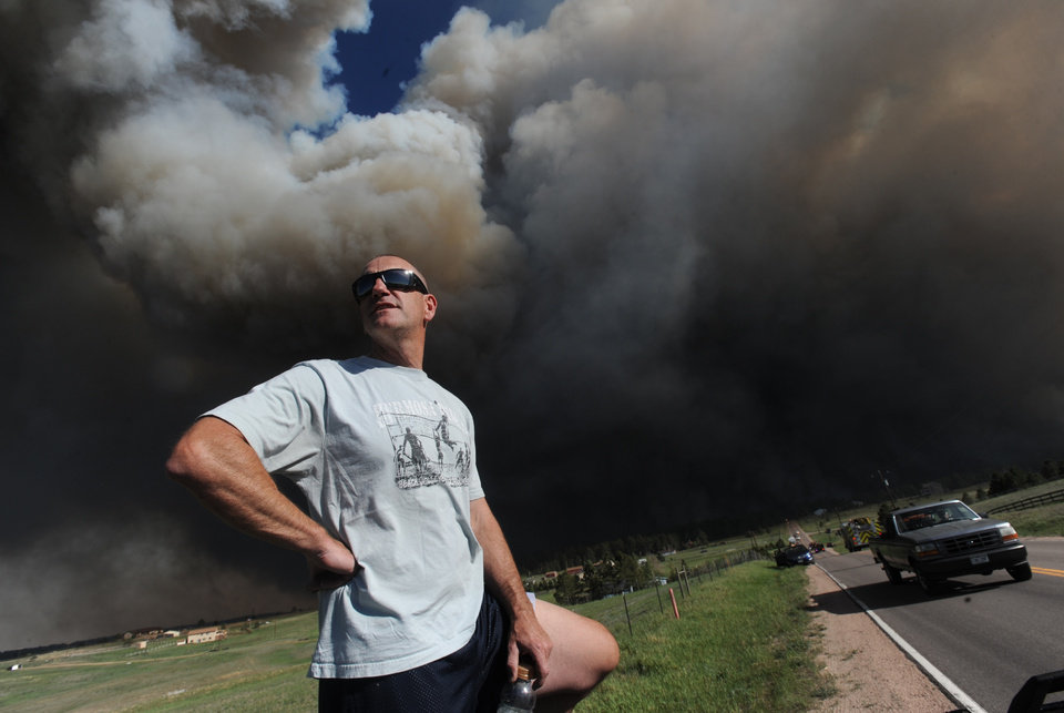 Photo - Dave Dunlap watches from the bed of his truck as a wildfire crosses Black Forest Road near his home Tuesday afternoon, June 11, 2013, in Colorado Springs, Colo. The Black Forest Fire was one of at least three significant wildfires burning in Colorado amid gusty winds and record-breaking hot, dry weather. (AP Photo/The Colorado Springs Gazette, Christian Murdock) MAGS OUT