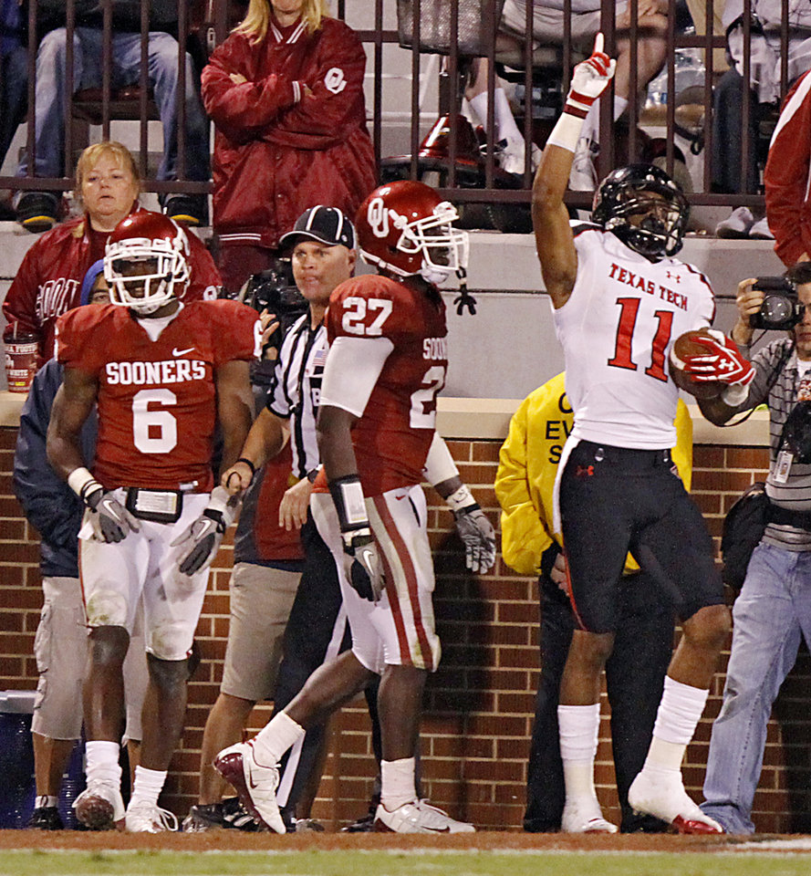 Photo - Texas Tech's Tramain Swindall (11) celebrates a touchdown in front of Oklahoma's Demontre Hurst (6) and Sam Proctor (27) during the college football game between the University of Oklahoma Sooners (OU) and Texas Tech University Red Raiders (TTU) at the Gaylord Family-Oklahoma Memorial Stadium on Saturday, Oct. 22, 2011. in Norman, Okla. Photo by Chris Landsberger, The Oklahoman