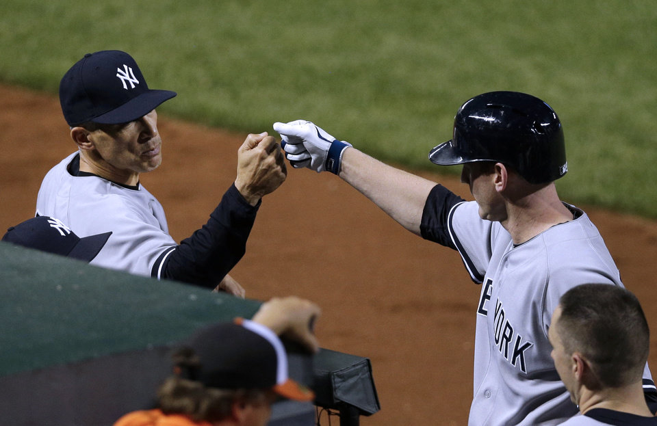 Photo - New York Yankees manager Joe Girardi, left, fist-bumps Lyle Overbay after he hit a solo home run in the seventh inning of a baseball game against the Baltimore Orioles in Baltimore, Monday, May 20, 2013. (AP Photo/Patrick Semansky)