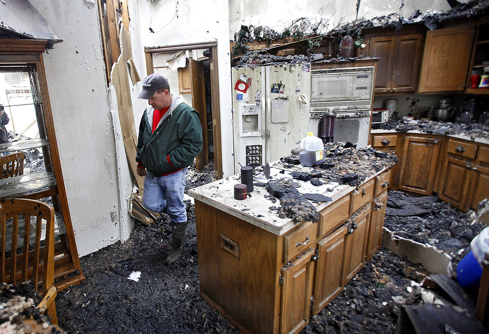 Photo - Charles Collier walks through his home as he looks over his destroyed home that was consumed by wildfires on Friday, April 10, 2009, in Midwest City, Okla.  Photo by Chris Landsberger, The Oklahoman