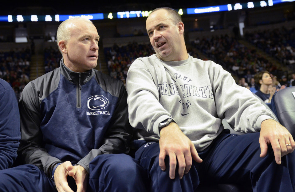 Photo - Penn State head men's basketball coach Patrick Chambers, left, and Penn State head football coach Bill O'Brien talk during a timeout of the Penn State against Connecticut women's NCAA college basketball game on Sunday, Nov. 17, 2013, in State College, Pa. Connecticut defeated Penn State  71 - 52. (AP Photo/John Beale)