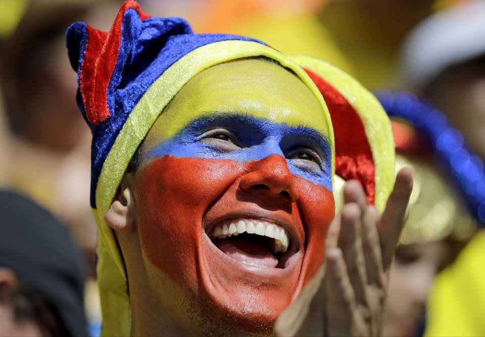 Photo - A Colombian supporter applauds before the group C World Cup soccer match between Colombia and Ivory Coast at the Estadio Nacional in Brasilia, Brazil, Thursday, June 19, 2014. (AP Photo/Sergei Grits)