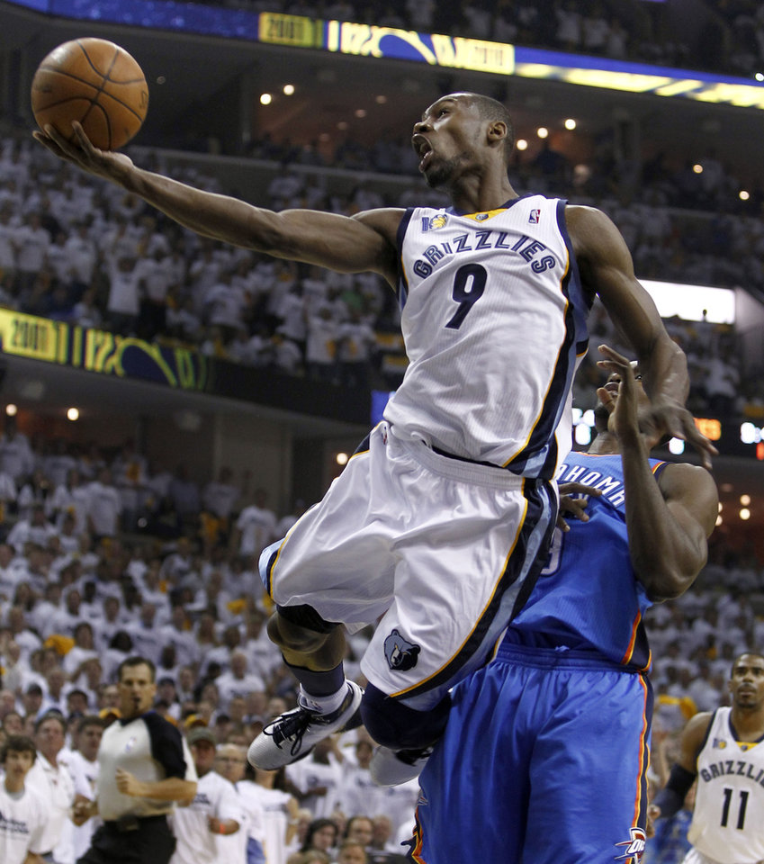 Photo - Memphis Grizzlies guard Tony Allen, left, scores against Oklahoma City Thunder forward Serge Ibaka during the first half of Game 4 of a second-round NBA basketball series on Monday, May 9, 2011, in Memphis, Tenn. (AP Photo/Wade Payne)