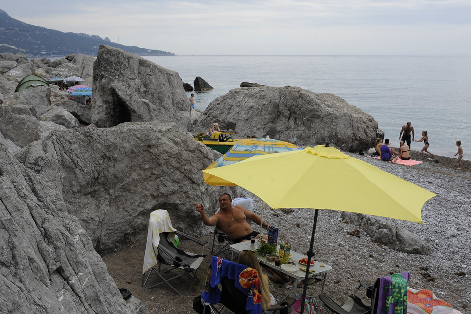 Photo - Russian tourists enjoy a Black Sea beach about 35 kms (22 miles) from Yalta, Crimea, Sunday, June 15, 2014. When Russia annexed the Black Sea peninsula of Crimea earlier this year, it regained not only harbors for its navy and abandoned Ukrainian military bases but also long stretches of pebble beaches that were the summer destination of choice for millions of Soviet citizens. The Kremlin is hoping to attract tourists to Crimea, which Russia annexed in March, by asking state-controlled companies to send their employees on free vacation trips.(AP Photo/Andrew Lubimov)