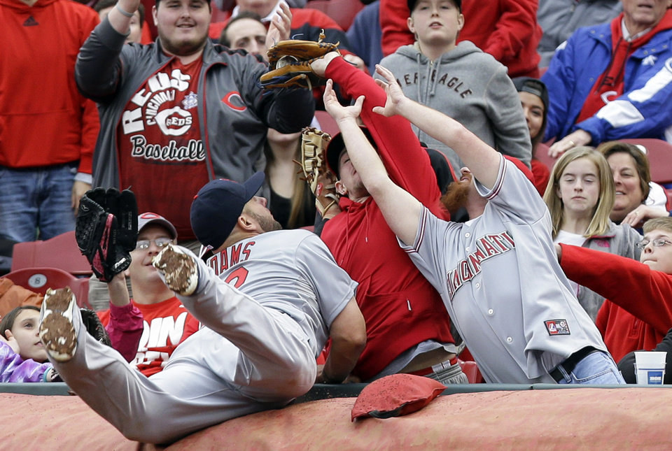 Photo - St. Louis Cardinals first baseman Matt Adams falls into the stands while trying to catch a foul ball hit by Cincinnati Reds' Chris Heisey that was caught by a fan in the third inning of a baseball game on Thursday, April 3, 2014, in Cincinnati. (AP Photo/Al Behrman)
