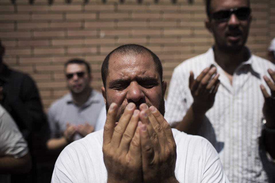 Photo - A friend of Ammar Badie, the son of Muslim Brotherhood's spiritual leader Mohammed Badie, who was killed Friday by Egyptian security forces during clashes in Ramses Square, cries while attending his burial in Cairo's Katameya district, Egypt, Sunday, Aug. 18, 2013. Egyptian authorities raided homes of Muslim Brotherhood members Sunday in an apparent attempt to disrupt the group ahead of mass rallies by supporters of the country's ousted president. (AP Photo/Manu Brabo)