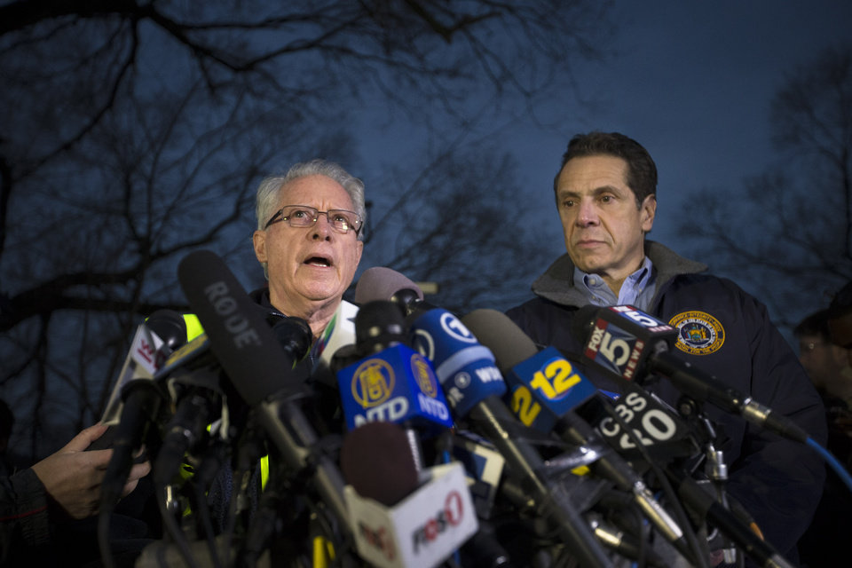 Photo - National Transportation Safety Board board member Earl Weener speaks during a news conference alongside New York Governor Andrew Cuomo, right, at the scene of a Metro-North passenger train derailment in the Bronx borough of New York, Sunday, Dec. 1, 2013. The train derailed on a curved section of track in the Bronx on Sunday morning, coming to rest just inches from the water and causing multiple fatalities and dozens of injuries, authorities said. Metropolitan Transportation Authority police say the train derailed near the Spuyten Duyvil station. (AP Photo/John Minchillo)