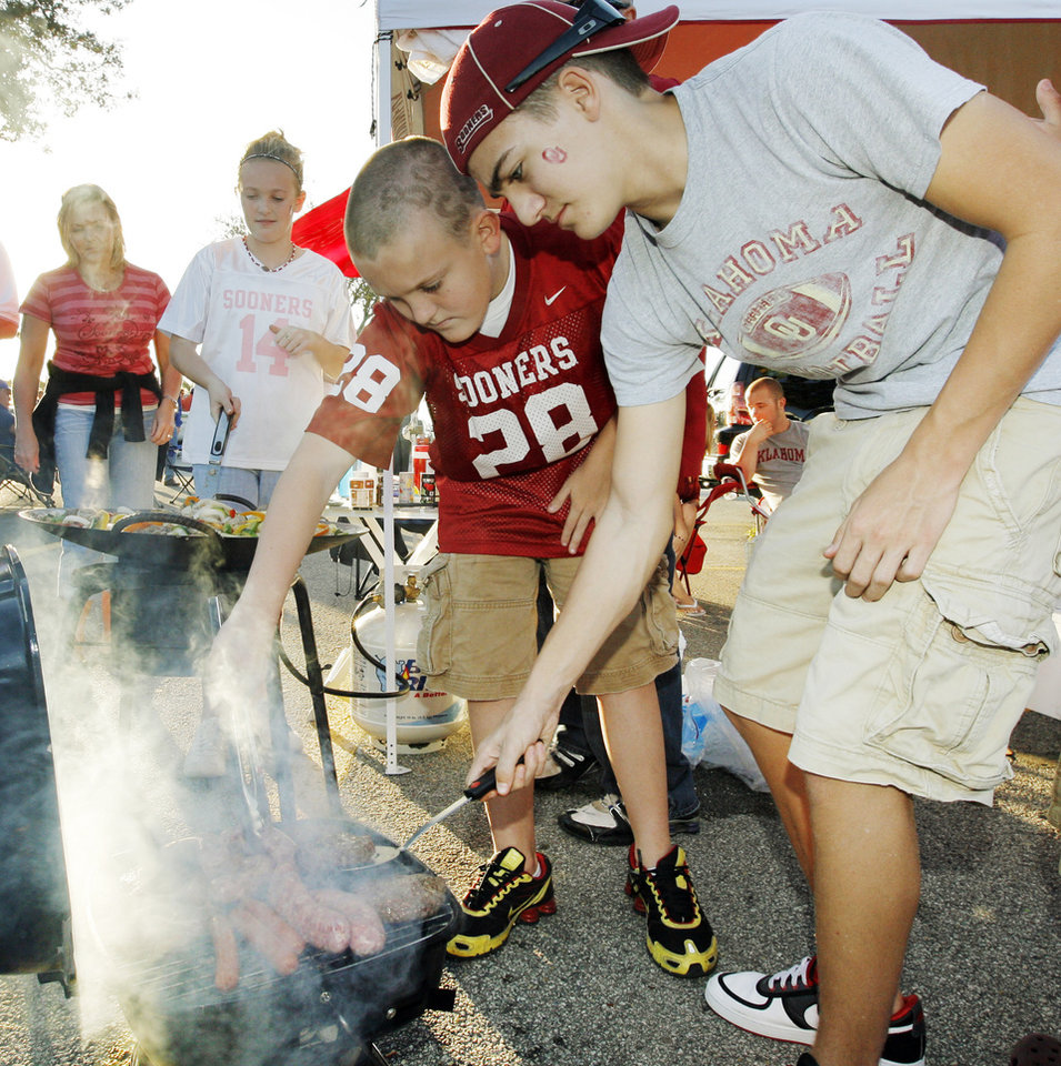 Photo - From right, siblings Braden Lutts, 15, Bryce Lutts, 12, and Rylee Lutts, 10, of Oklahoma City, check food on grills while cooking in the parking lot before the BCS National Championship college football game between the University of Oklahoma Sooners (OU) and the University of Florida Gators (UF) on Thursday, Jan. 8, 2009, at Dolphin Stadium in Miami Gardens, Fla. 