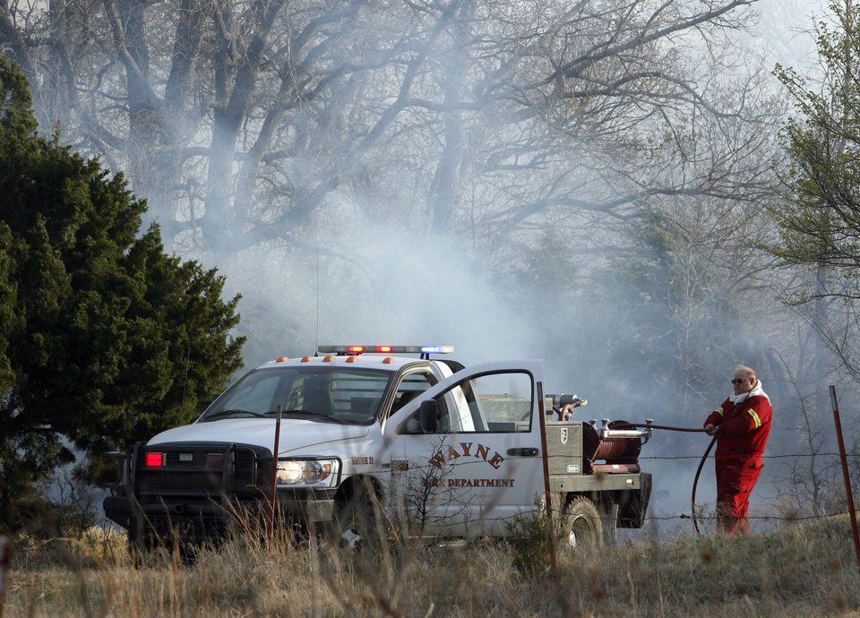 Photo - A firefighter from Wayne pulls hose to douse hot spots where wildfires destroyed 12 structures in Lindsay, Okla., on Thursday, April 9, 2009.  Photo by Steve Sisney, The Oklahoman