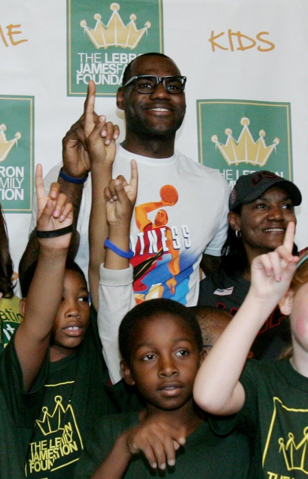 Photo -   NBA star and Akron native LeBron James and his mother Gloria James, right, pose with children participating in the LeBron James Family Foundation's Wheels for Education