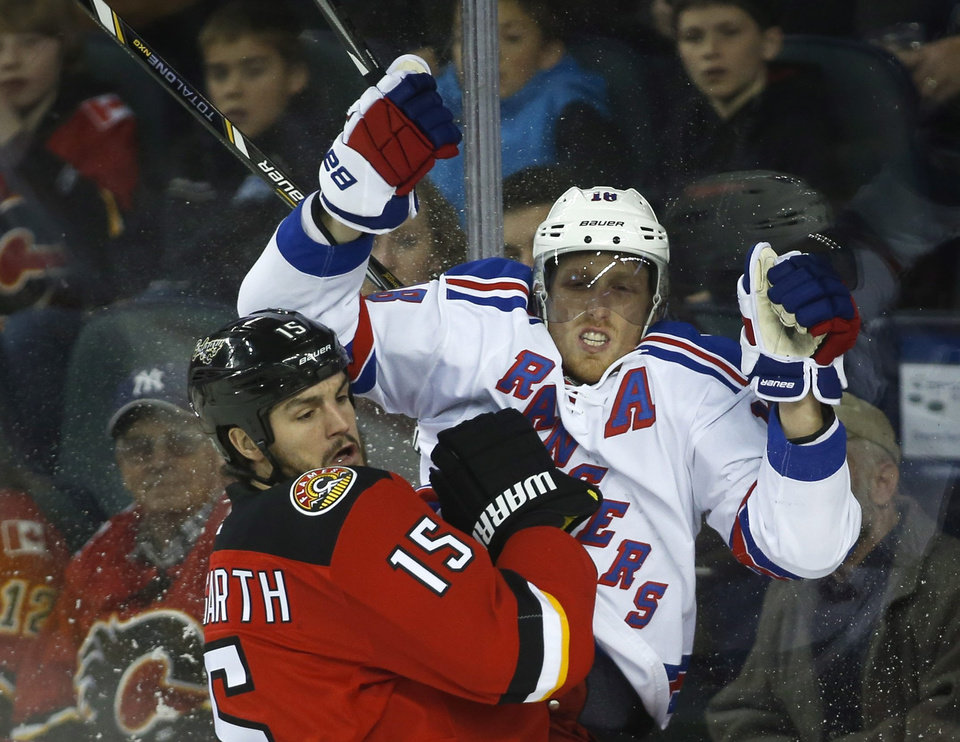 Photo - New York Rangers' Marc Staal, right, is checked by Calgary Flames' Kevin Westgarth during the first period of an NHL hockey game in Calgary, Alberta, Friday, March 28, 2014. (AP Photo/The Canadian Press, Jeff McIntosh)