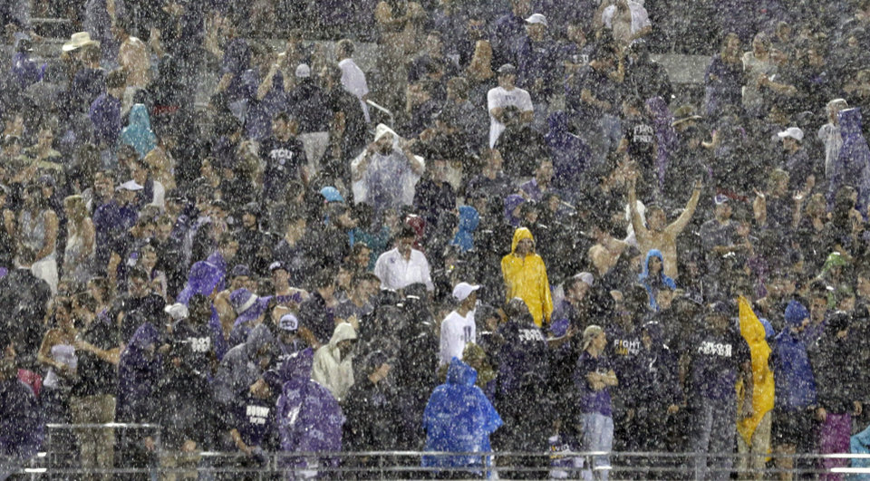 Photo - Fans sit in the stands in a heavy rain during a thunder delay in the second quarter of an NCAA college football game between Texas and TCU, Saturday, Oct. 26, 2013, in Fort Worth, Texas. (AP Photo/LM Otero)