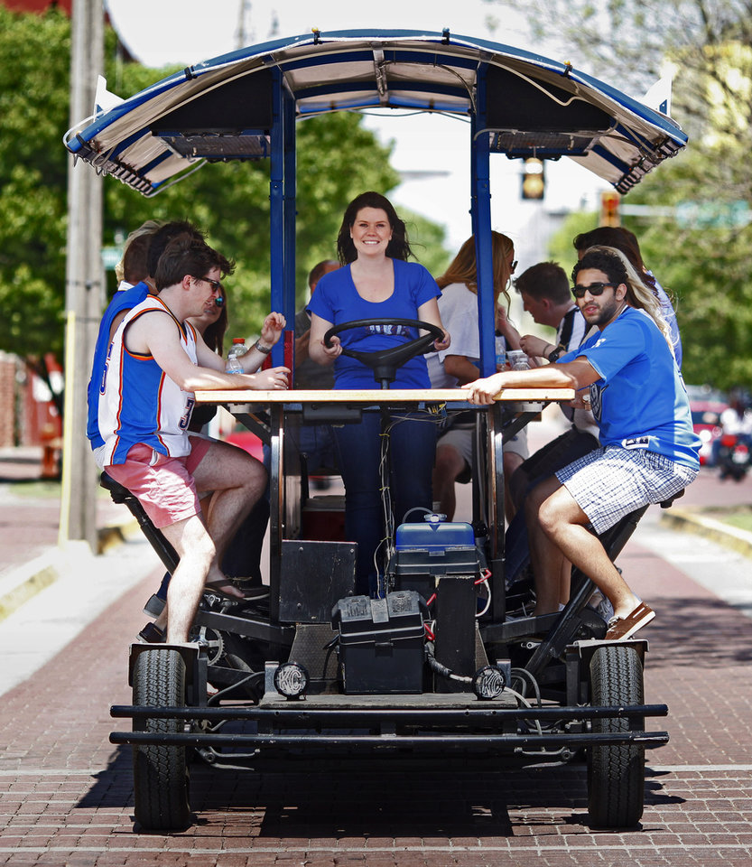 Photo -  Danielle Higginbotham drives the Bricktown Bike Bar around Bricktown while riders pedal and drink in Oklahoma City.     -