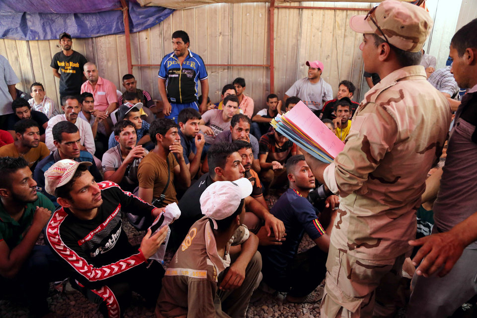 Photo - Iraqi men check in at main army recruiting center to volunteer for military service in Baghdad, Iraq, Friday, June 20, 2014, after authorities urged Iraqis to help battle insurgents. The campaign by the al-Qaida-inspired Islamic State militants has raised the specter of the sectarian warfare that nearly tore the country apart in 2006 and 2007, with the popular mobilization to fight the insurgents taking an increasingly sectarian slant, particularly after Iraq's top Shiite cleric made a call to arms last week. (AP Photo/Karim Kadim)