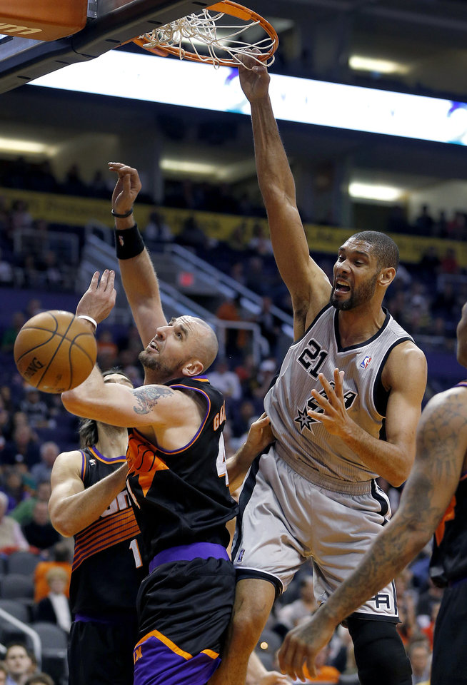 San Antonio Spurs\' Tim Duncan dunks over Phoenix Suns\' Marcin Gortat, of Poland, during the first half of an NBA basketball game, Sunday, Feb. 24, 2013, in Phoenix. (AP Photo/Matt York)