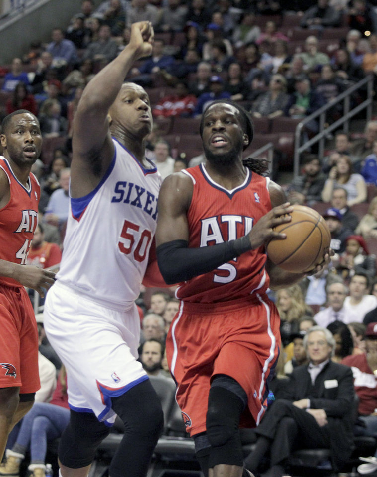 Photo - Atlanta Hawks' DeMarre Carroll (5) looks to pass as Philadelphia 76ers' Lavoy Allen (50) defends in the first half of an NBA basketball game, Friday, Jan. 31, 2014, in Philadelphia. (AP Photo/H. Rumph Jr.)
