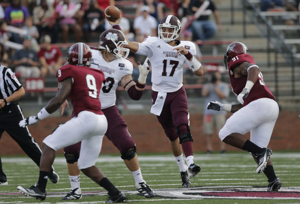 Photo -   Mississippi State quarterback Tyler Russell (17) passes the ball as Troy defensive tackle Shermane TeArt (91) pursues in the first half of an NCAA college football game in Troy, Ala., Saturday, Sept. 15, 2012. (AP Photo/Dave Martin)
