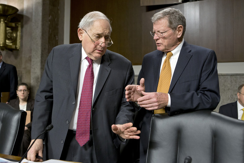 Photo - Senate Armed Services Committee Chairman Sen. Carl Levin, D-Mich., left, and the committee's ranking Republican, Sen. James Inhofe, R-Okla., confer on Capitol Hill in Washington, Thursday, Feb. 14, 2013, before the start of a hearing. Republicans on the panel have been vocal in their opposition to the nomination of Chuck Hagel to be the next secretary of defense. While Democrats hold a 55-45 edge in the Senate and have the numbers to confirm Hagel on a majority vote, they need the support of five Republicans to clear the way for an up-or-down vote on him. (AP Photo/J. Scott Applewhite)