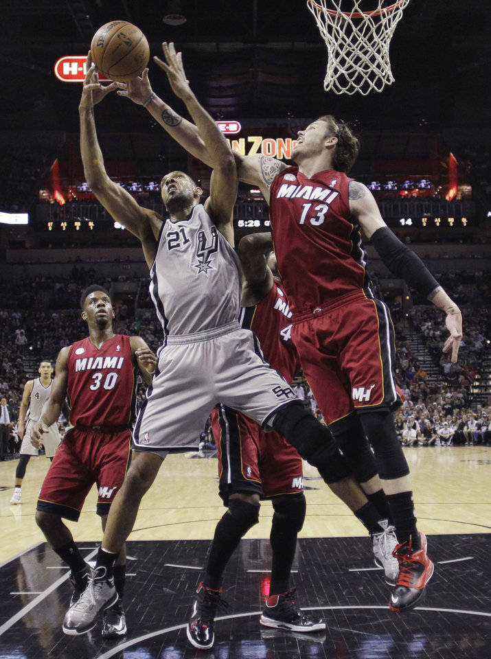 Photo - San Antonio Spurs' Tim Duncan (21) and Miami Heat's Mike Miller (13) reach for a rebound during the first half of an NBA basketball game, Sunday, March 31, 2013, in San Antonio. (AP Photo/Eric Gay)