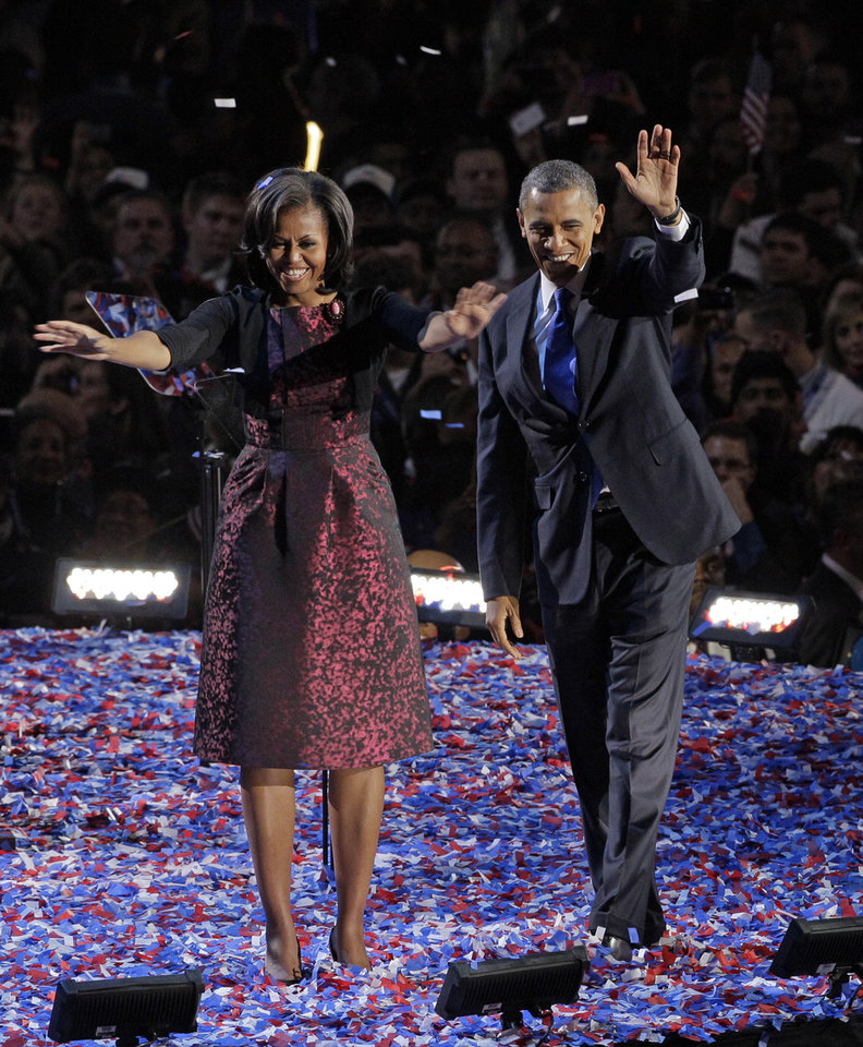 Photo -   FILE - This file photo taken Nov. 6, 2012 in Chicago shows President Barack Obama along with first lady Michelle Obama acknowledging the crowd at his election night party. As Michelle Obama stepped on stage , she accepted her role not only as first lady but fashion tastemaker for four more years.(AP Photo/Nam Y. Huh, file)