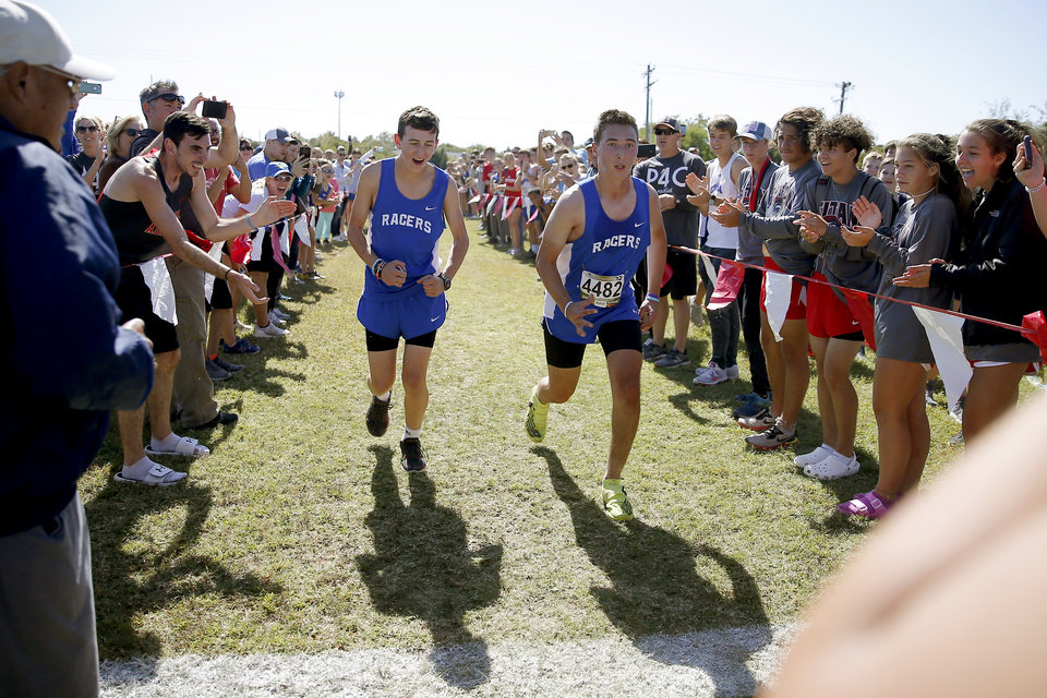 Photo - Newcastle runner Caleb Freeman, at right, who was injured in a 2017 car crash, finishes a cross country race beside his brother Clayton Freeman, 16, at Carl Albert in Midwest City, Okla., Tuesday, Oct. 8, 2019. This was Caleb Freeman's first cross country race since getting injured in a 2017 car wreck. [Bryan Terry/The Oklahoman]