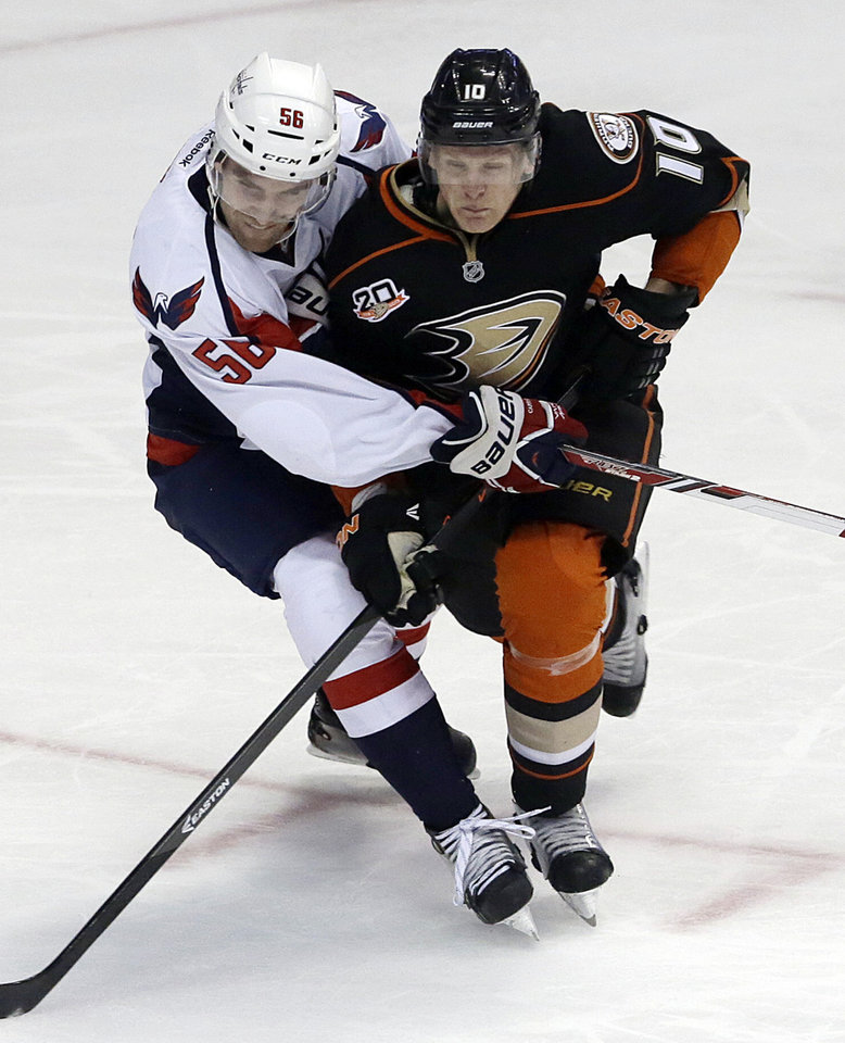 Photo - Anaheim Ducks right winger Corey Perry (10) and Washington Capitals defenseman Patrick Wey (56) tangle during the second period of an NHL hockey game Tuesday, March 18, 2014, in Anaheim, Calif. (AP Photo/Reed Saxon)