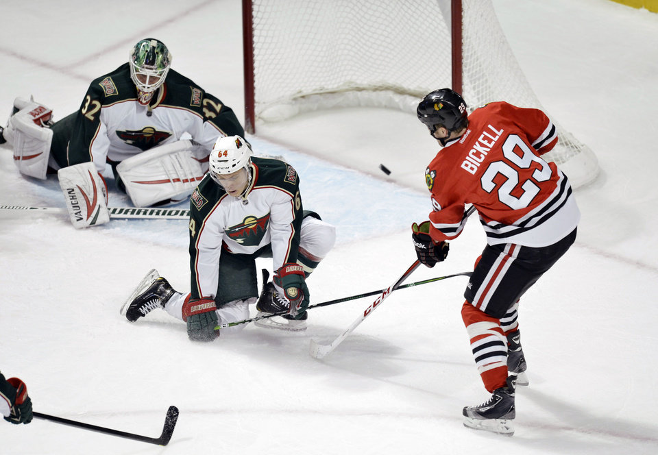 Chicago Blackhawks left wing Bryan Bickell, left to right, scores past Minnesota Wild center Mikael Granlund of Finland, and goalie Niklas Backstrom of Finland during the first period of an NHL hockey game, Tuesday, March 5, 2013 in Chicago.  (AP Photo/Brian Kersey)