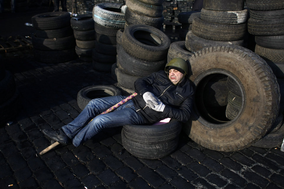 Photo - An anti-government protester catches some sleep on a barricade at Independence Square in Kiev, Ukraine, Friday, Feb. 21, 2014. Ukraine's presidency said Friday that it has negotiated a deal intended to end battles between police and protesters that have killed scores and injured hundreds, but European mediators involved in the talks wouldn't confirm a breakthrough. (AP Photo/ Marko Drobnjakovic)