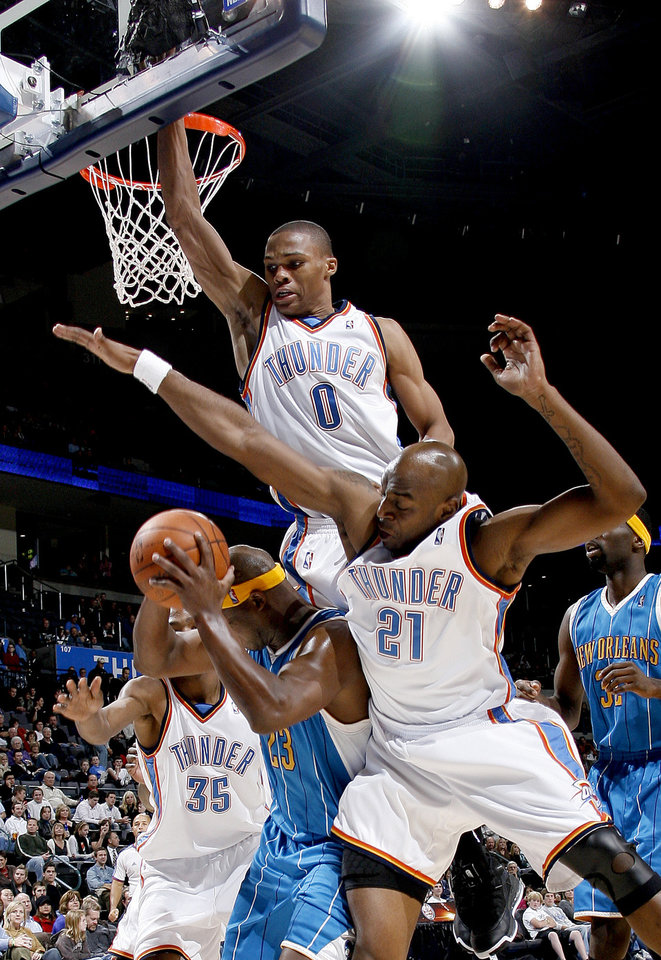 Photo - Oklahoma City's Kevin Durant, left, Russell Westbrook, and Damien Wilkins foul Devin Brown of the Hornets during the NBA basketball game between the Oklahoma City Thunder and the New Orleans Hornets at the Ford Center in Oklahoma City on Friday, Nov. 21, 2008.   BY BRYAN TERRY, THE OKLAHOMAN ORG XMIT: KOD