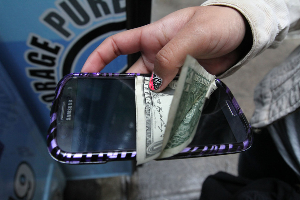 Photo -   In this Sept. 27, 2012 photo, a student holds an electronic device along with payment of a dollar to store it for the day in the Pure Loyalty Electronic Device Storage truck parked near the Washington Irving educational complex in New York. Cellphones are banned in all New York City public schools, but the rule is widely ignored except in schools with metal detectors. Outside those schools, entrepreneurs park trucks where students drop off electronic devices before class and get them back at the end of the day.(AP Photo/Tina Fineberg)