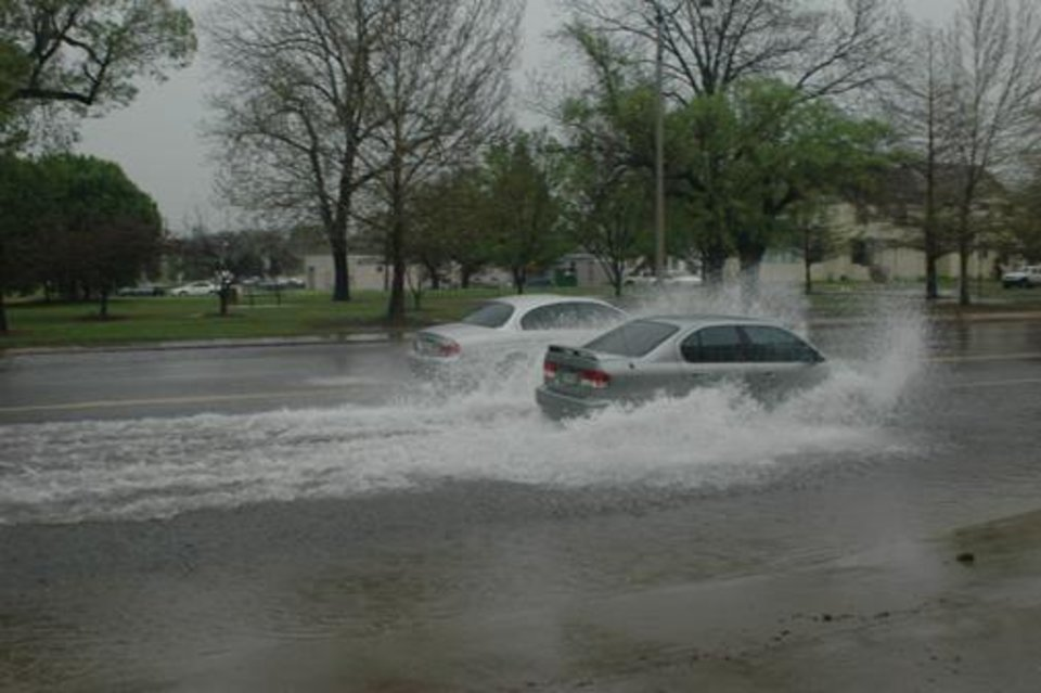 Cars driving through the water on Broadway and 11th Street in Downtown OKC<br/><b>Community Photo By:</b> Russel Hamm<br/><b>Submitted By:</b> Russel, Oklahoma City