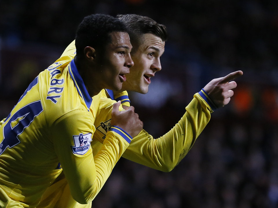 Photo - Arsenal's Jack Wilshere, right, celebrates with teammate Serge Gnabry after scoring a goal against during the English Premier League soccer match between Aston Villa and Arsenal at Villa Park stadium in Birmingham, England, Monday, Jan. 13, 2014. (AP Photo/Kirsty Wigglesworth)