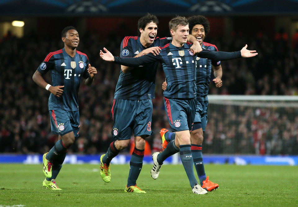 Photo - Munich's Toni Kroos, front celebrates his side's opening goal with David Alaba, Javier Martinez and Dante, from left,  during a Champions League, round of 16, first leg soccer match between Arsenal and Bayern Munich at the Emirates stadium in London, Wednesday, Feb. 19, 2014 .(AP Photo/Alastair Grant)