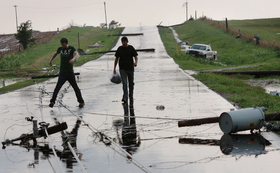 Shawn Webb, left, of Coyle, and friend, Matthew Moglia of Stillwater, step over downed lines after utility poles were snapped on SH 74F east of Cashion. by a tornado that came through the area Tuesday afternoon, May 24, 2011, The pair was storm chasing when they were caught in the tornado as it crossed the roadway. The winds forced their truck into a ditch. Neither was injured. Photo by Jim Beckel, The Oklahoman