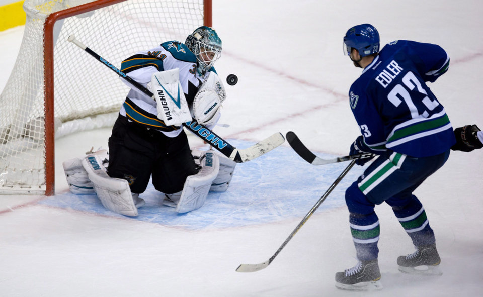 Photo - San Jose Sharks goalie Antti Niemi, left, of Finland, stops Vancouver Canucks' Alexander Edler, of Sweden, during the overtime period of an NHL hockey game in Vancouver, British Columbia, Tuesday, March 5, 2013. (AP Photo/The Canadian Press, Darryl Dyck)