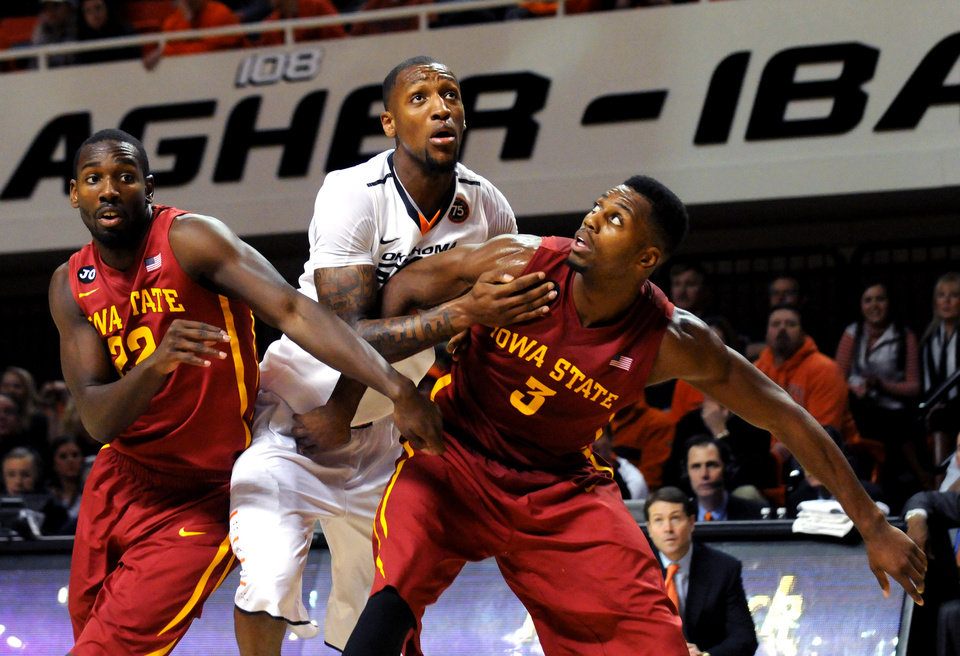 Photo - Iowa State's Dustin Hogue, left, and Melvin Ejim, right, block out Oklahoma State's Kamari Murphy, center, during an NCAA college basketball game in Stillwater, Okla., Monday, Feb. 3, 2014. Hogue scored 13 points in the 98-97 triple overtime win over Oklahoma State. (AP Photo/Brody Schmidt)