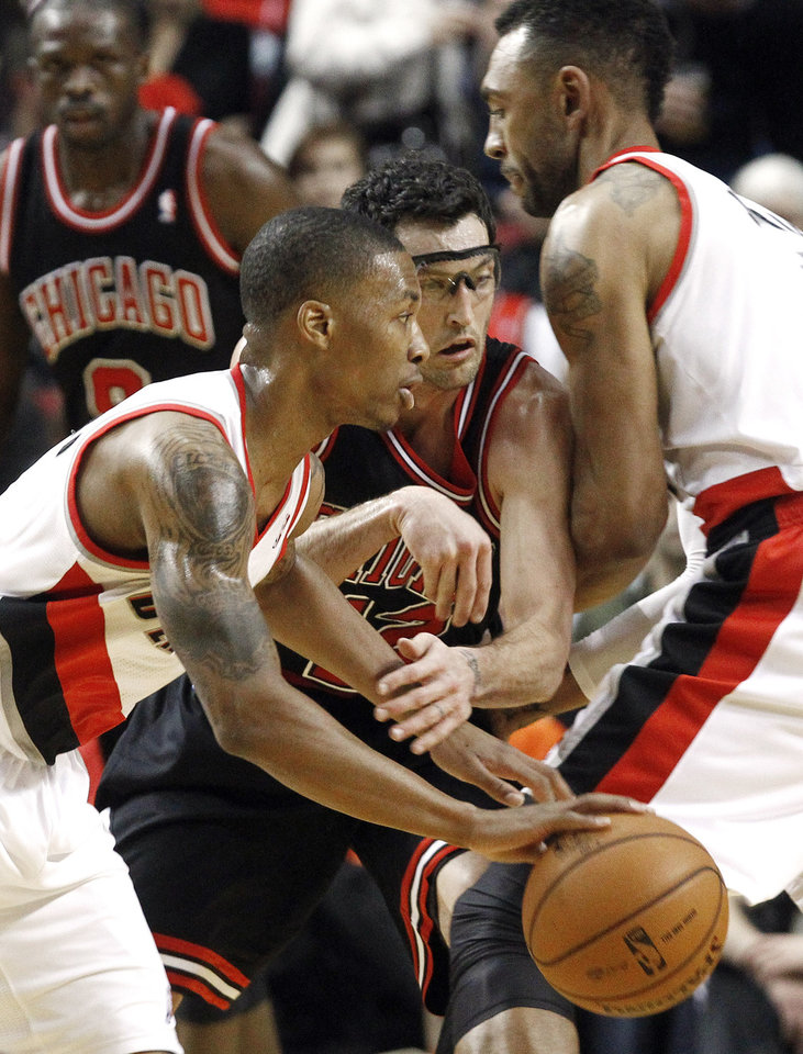 Photo -   Portland Trail Blazers guard Damian Lillard, left, drives on Chicago Bulls guard Kirk Hinrich, middle, as he is screened out by Trail Blazers forward Jared Jeffries during the first quarter of their NBA basketball game in Portland, Ore., Sunday, Nov. 18, 2012. (AP Photo/Don Ryan)
