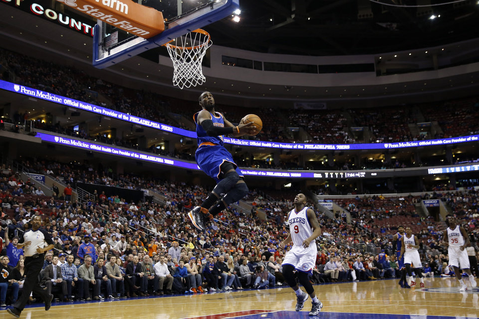 Photo - New York Knicks' Tim Hardaway Jr., center, goes up for a dunk as Philadelphia 76ers' James Anderson looks on during the first half of an NBA basketball game, Friday, March 21, 2014, in Philadelphia. (AP Photo/Matt Slocum)