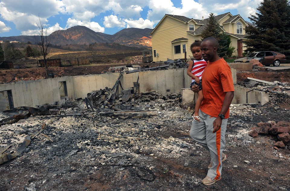 Immanuel Mgana holds his daughter Grace Mgana, 2, as he surveys what is left of their home Sunday, July 1, 2012, into the Mountain Shadows subdivision of Colorado Springs, Colo., after the Waldo Canyon fire ravaged the neighborhood. Immanuel had been deployed in the army in East Africa but was allowed to return home when he got word of the damage. So far, the blaze, now 45 percent contained, has damaged or destroyed nearly 350 homes. (AP Photo/The Denver Post, Helen H. Richardson) MAGS OUT; TV OUT; INTERNET OUT
