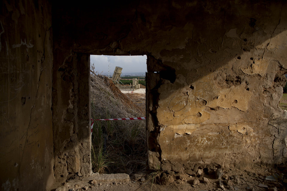 Photo -   A military Iron Dome defense missile system, designed to intercept and destroy incoming short-range rockets and artillery shells from Gaza, is seen through an abandoned house near Tel Aviv Sunday, Nov. 18, 2012. (AP Photo/Oded Balilty)