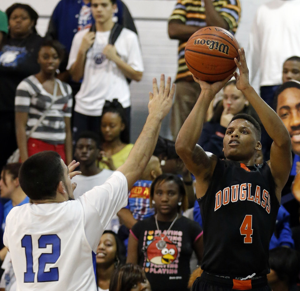 Douglass\' Deangleo Smith shoots over Southeast\'s Ricardo Deluna during the high school basketball game between Southeast and Douglass at Southeast High School in Oklahoma City, Tuesday, Jan. 29, 2013.Photo by Sarah Phipps, The Oklahoman