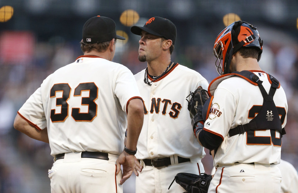 Photo - San Francisco Giants pitcher Ryan Vogelsong, center, receives a visit from pitching coach Dave Righetti (33) and catcher Buster Posey during the sixth inning of a baseball game against the Los Angeles Dodgers, Saturday, July 26, 2014, in San Francisco. (AP Photo/Beck Diefenbach)