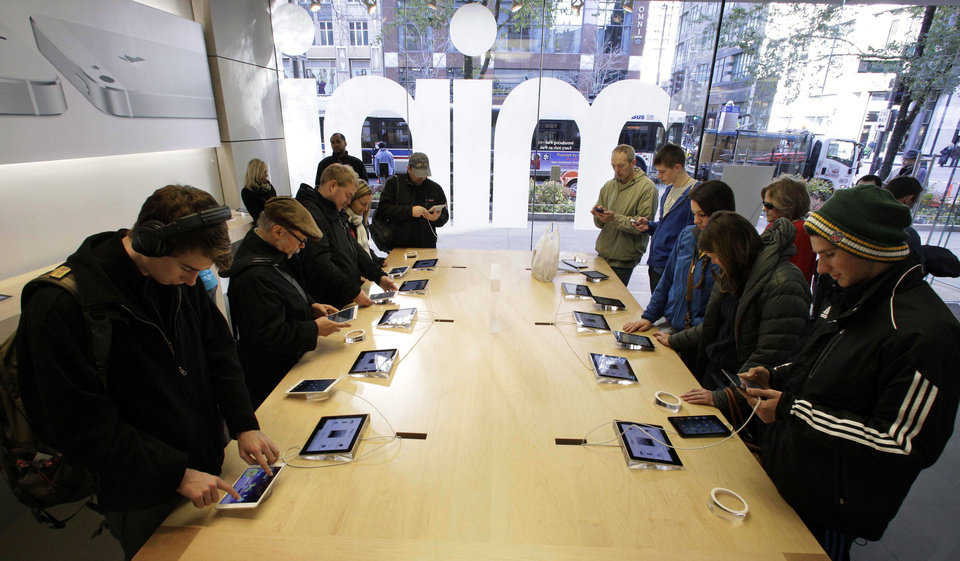 FILE - In this Friday, Nov. 2, 2012 file photo, Shoppers check out the new Apple iPad mini at the Apple store on Michigan Ave. in Chicago. Apple said Monday, Nov. 5, 2012, it sold 3 million iPads of all kinds in the first three days it sold the new Mini model. (AP Photo/M. Spencer Green, FIle)