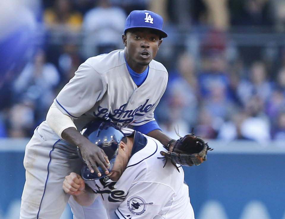 Photo - San Diego Padres' Seth Smith runs into Los Angeles Dodgers second baseman Dee Gordon while trying to break up a double play in the sixth inning of a baseball game Tuesday, April 1, 2014, in San Diego.  The Dodgers completed the double play. (AP Photo/Lenny Ignelzi)
