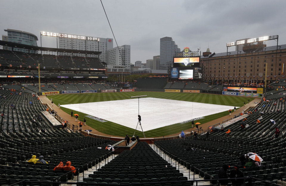 A tarp covers the infield as rain falls before Game 1 of the American League division baseball series between the Baltimore Orioles and the New York Yankees on Sunday, Oct. 7, 2012, in Baltimore. (AP Photo/Patrick Semansky)