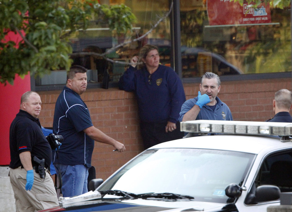 Photo -   Police investigate the shooting of three people in a Pathmark supermarket on Route 9 in Old Bridge, N.J., Friday, Aug. 31, 2012. Officials say a supermarket employee killed two people at the store early Friday and then fatally shot himself. Authorities say he opened fire on employees he saw when he walked into the Pathmark store. The store's front windows were shattered by gunfire. The motive is being investigated. (AP Photo/Rich Schultz)