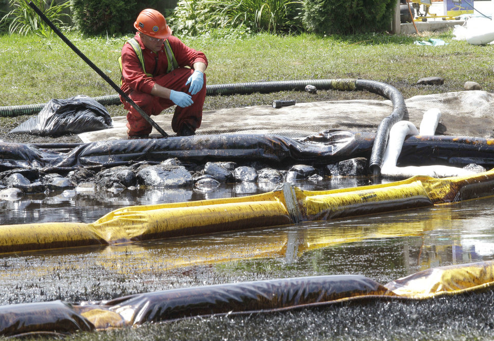 Photo -   FILE - In this July 29, 2010, file photo, a worker monitors water in Talmadge Creek in Marshall Township, Mich., near the Kalamazoo River as oil from a ruptured pipeline, owned by Enbridge Inc., is attempted to be trapped by booms. Federal investigators are expected to present their findings Tuesday, July 10, 2012 on the likely cause of a pipeline rupture that spilled more than 800,000 gallons of crude oil into the river nearly two years ago. (AP Photo/Paul Sancya, File)