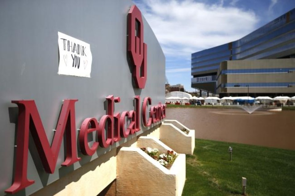 Photo -  A sign for medical workers is placed on the sign of the OU Medical Center in Oklahoma City,  Saturday, March 28, 2020.  [Sarah Phipps/The Oklahoman]