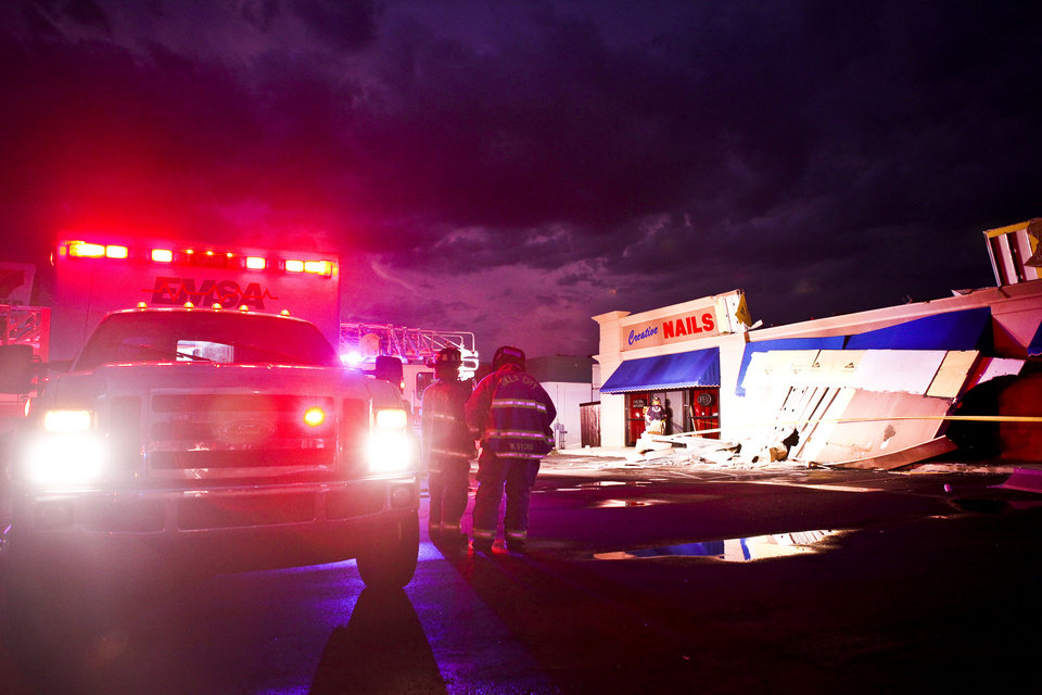 Photo - The upper part of the exterior wall of a yet-to-be opened liquor store called Mixed Delights collapsed and pinned the right leg of an ADT worker installing an alarm before emergency crews could cut him out near the corner of Britton road and MacArthur Boulevard after a thunderstorm with high winds hit on Monday, August 8, 2011. Photo by Zach Gray ORG XMIT: KOD